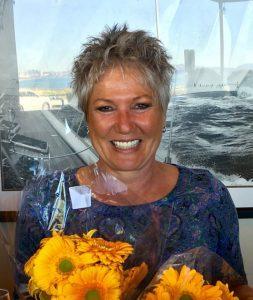 Peta Sanderson smiling holding flowers